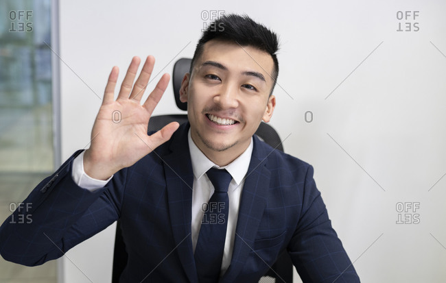 Positive young Asian male executive manager in business style wear looking at camera and waving hand while sitting in office