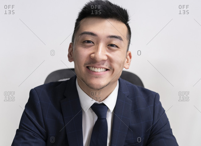 Positive young Asian male executive manager in business style wear looking at camera while sitting in office
