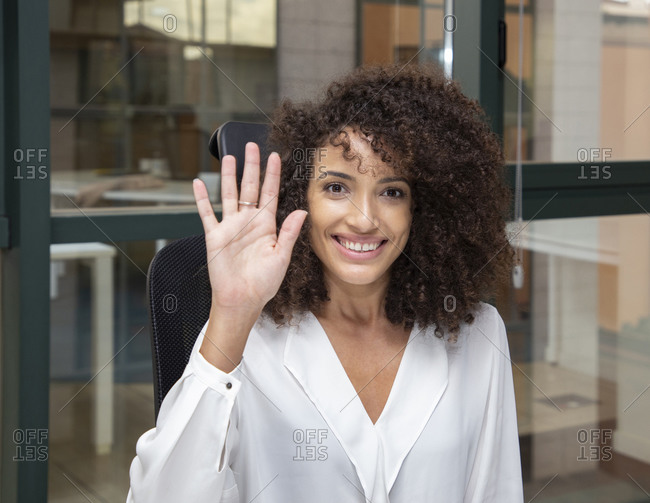 Young ethnic businesswoman with afro hairstyle sitting at desk while looking at camera waving hand