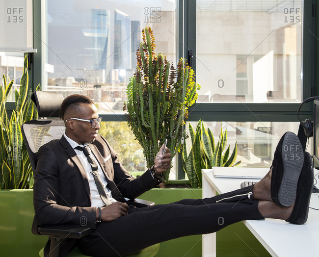 Full body side view of positive young ethnic black male employee in casual outfit sitting on chair with legs on table and messaging on smartphone while resting during break in modern workspace