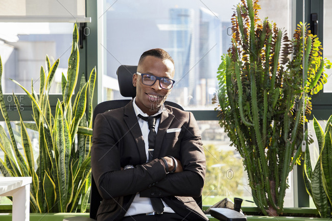 Positive young ethnic black male employee in casual outfit sitting on chair resting during break in modern workspace looking at camera