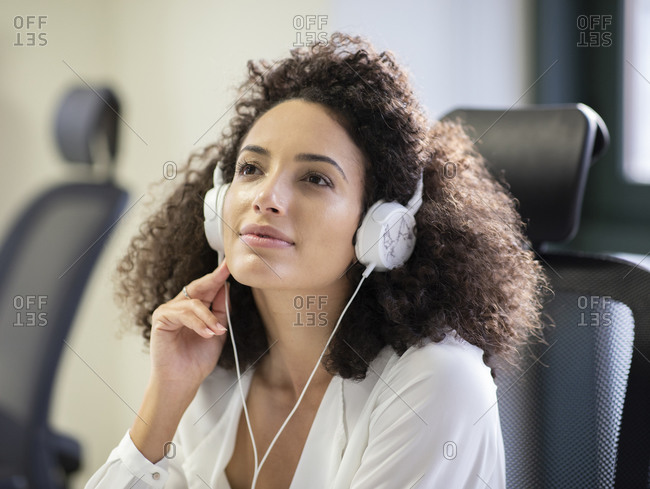 Young thoughtful Hispanic female employee in white blouse and headphones looking away while working at table with computer in modern workplace