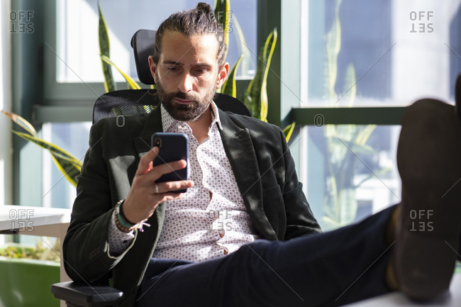 Concentrated adult bearded male entrepreneur in formal suit reading messages on mobile phone while sitting near window and having break during work in contemporary workspace
