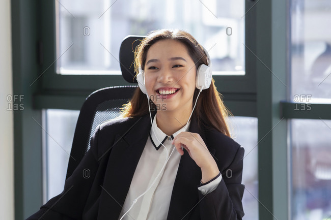 Happy young Asian female office employee in formal outfit and headphones laughing while having online conversation in modern office