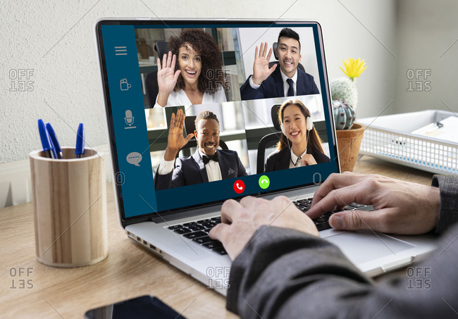 Crop anonymous businessman sitting at table with laptop in office and communicating with multiracial colleagues via video conference