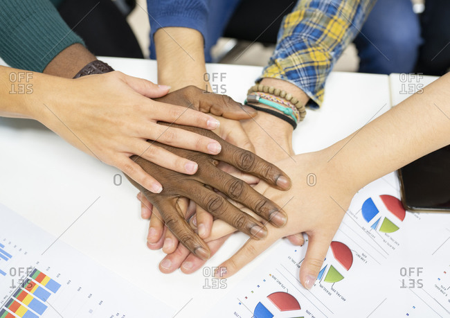 From above of crop anonymous multiracial colleagues in casual clothes gathering around table with charts and stacking hands together while working on business development plan in workplace