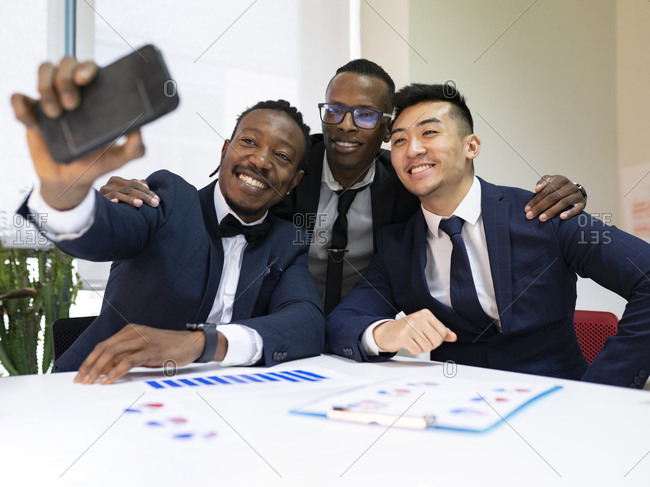 Group of smiling multiracial male business colleagues in formal suits gathering near table with diagrams and taking selfie on mobile phone during meeting in modern office