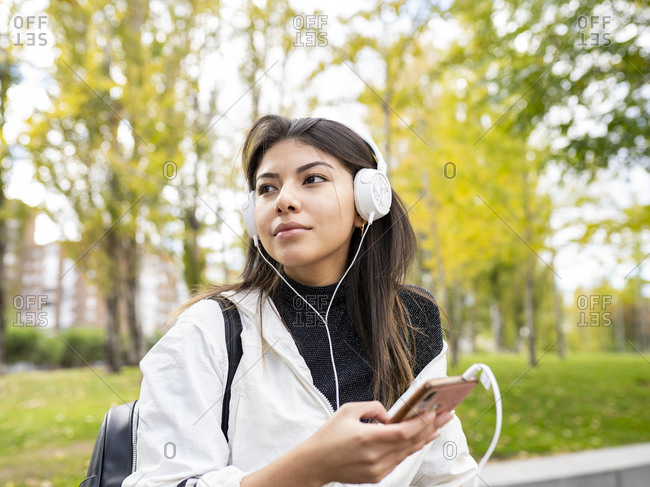 From below of positive young ethnic female in casual outfit listening to music with headphones and browsing mobile phone while chilling in park