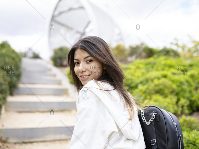 Side view of lonely contemplative young Latin female in trendy casual outfit standing on stairs and looking at camera thoughtfully
