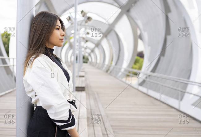 Side view of lonely contemplative young Latin female in trendy casual outfit standing on modern footbridge and looking away thoughtfully