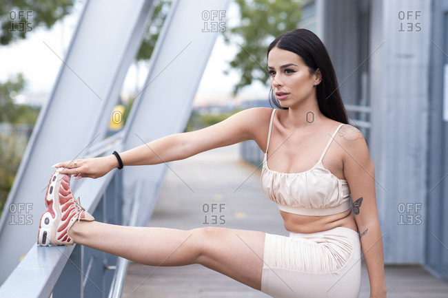 Side view of attractive young slim female in stylish sports outfit and sneakers doing stretching exercise for legs while standing near metal railing during fitness training on street