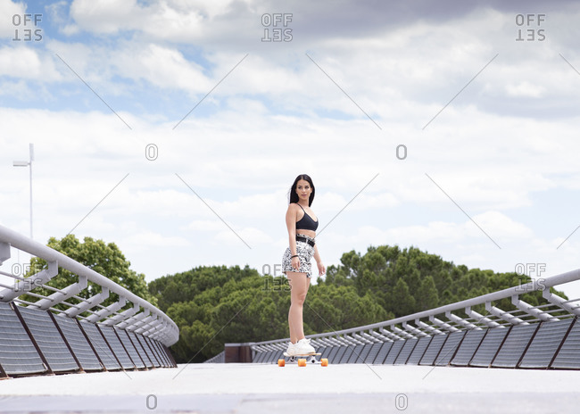 Full body of fit young female in trendy activewear skating on longboard along fenced bridge while practicing active lifestyle in summertime