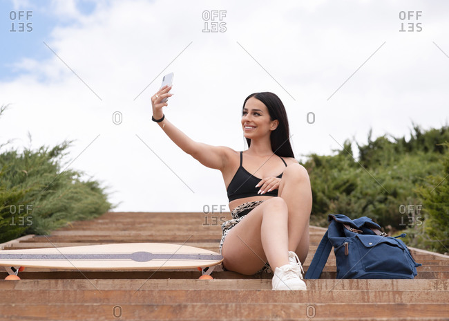 Low angle full length of smiling young fit female in activewear sitting on stairs near longboard and taking selfie on mobile phone
