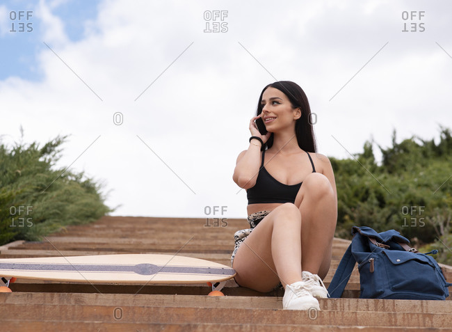 Low angle full length of smiling young fit female in activewear sitting on stairs near longboard and talking on mobile phone