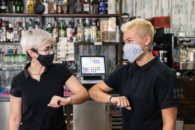 Delighted waitresses in uniform and protective masks greeting each other while bumping elbows at work in cafe during coronavirus epidemic