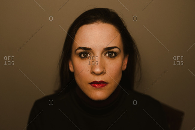 Serious young brunette looking at camera thoughtfully while standing against brown wall
