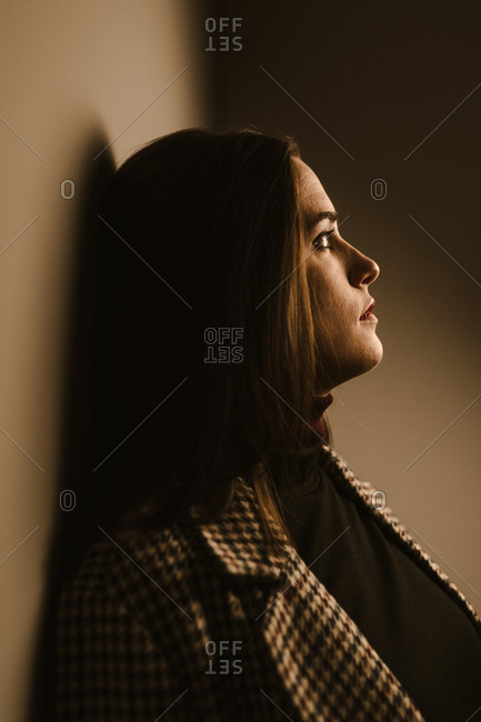 Side view of sad lonely young brunette in trendy checkered coat looking away thoughtfully while leaning back against brown wall
