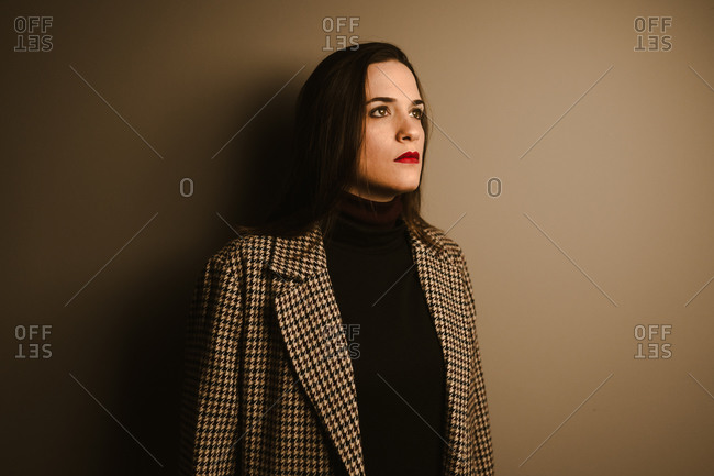 Sad lonely young brunette in trendy checkered coat looking away thoughtfully while standing against brown wall