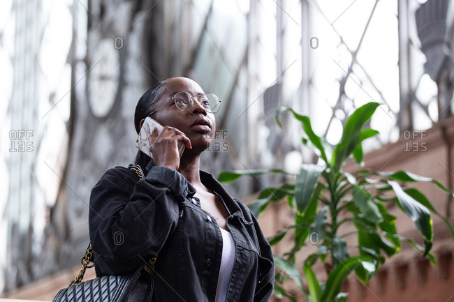 Low angle of serious young African American female in denim jacket and eyeglasses having phone conversation while standing near city building