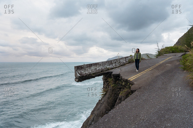 Unrecognizable distant asian ethnic female traveler standing on edge of destroyed asphalt road running along rough rocky coast near waving sea in overcast weather