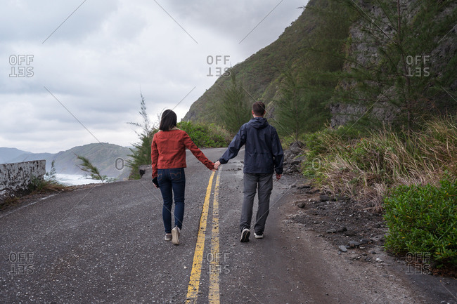 Back view of unrecognizable couple of travelers in activewear strolling on half destroyed asphalt road on coastline in overcast weather with storming sea