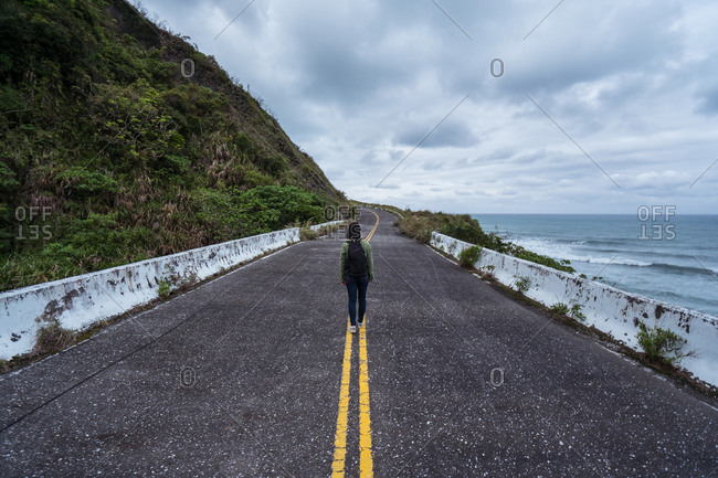 Back view of unrecognizable active female hiker with backpack walking on asphalt road leading along rocky coast in stormy weather with waving sea