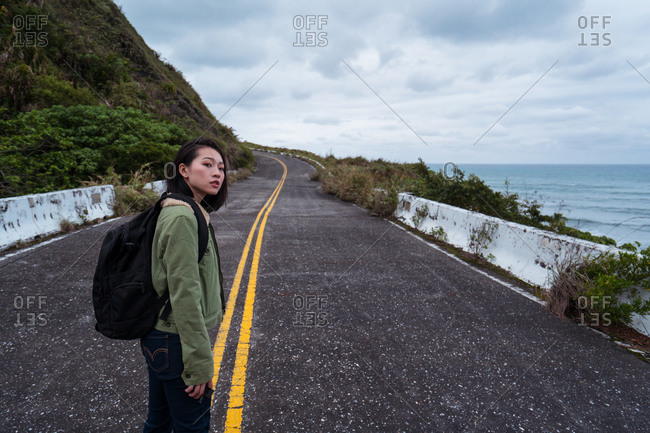 Side view of active female hiker with backpack walking on asphalt road leading along rocky coast in stormy weather with waving sea looking away
