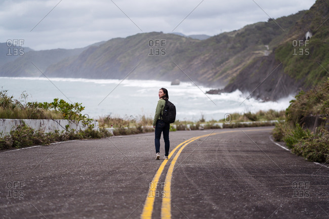 Back view of active female hiker with backpack walking on asphalt road leading along rocky coast in stormy weather with waving sea