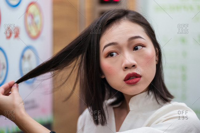 Young worried Asian female having problems and touching thin hair while looking away