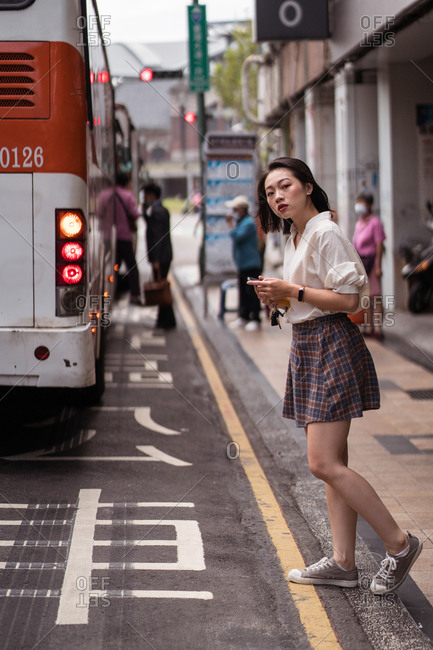 Side view of calm Asian female in casual style clothes walking crossing the street and looking away holding mobile phone in Taichung city