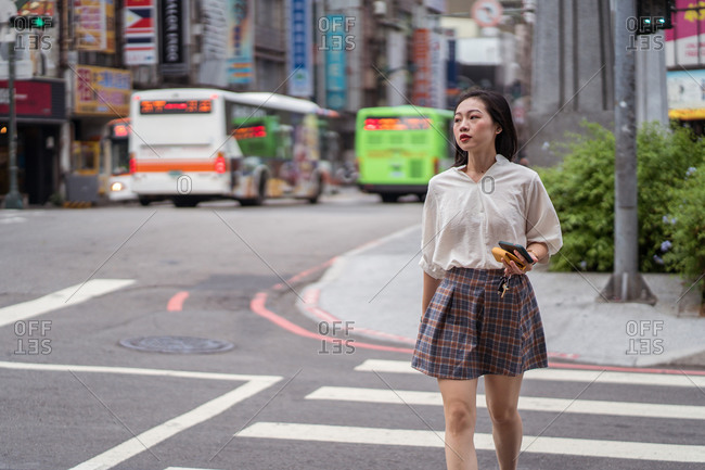 Calm Asian female in casual style clothes walking along crosswalk and looking away in Taichung city