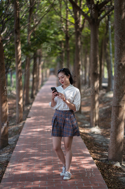 Smiling Asian female standing on alley and texting messages on smartphone while relaxing in Tanya Shen Green Bikeway in summer