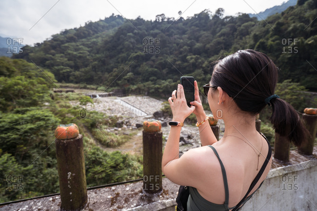 Back view of unrecognizable female tourist taking picture of highland terrain duding summer vacation in Taichung