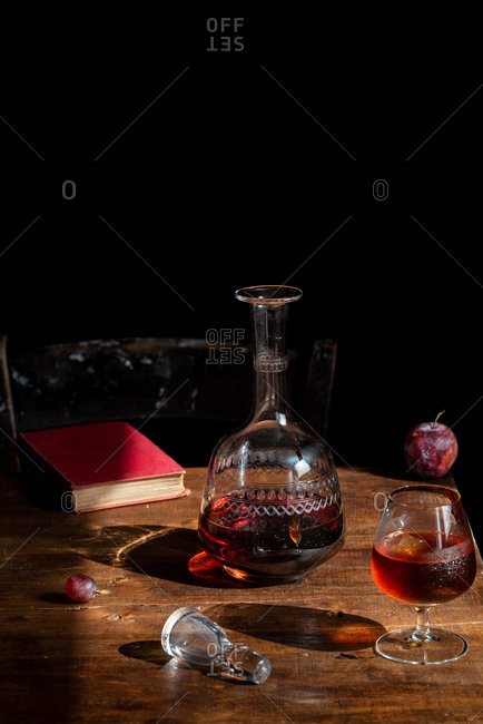 Glass of cognac with ice cubes placed on wooden table with decanter and fresh plum