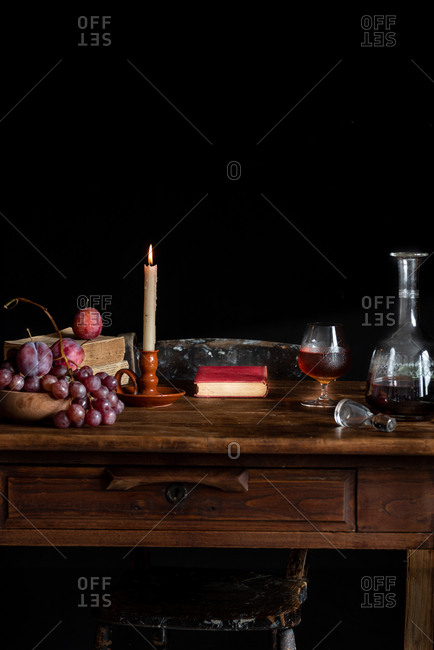 Old wooden table with alcohol beverage and fresh fruits placed near books and burning candle in cozy dark room with black background