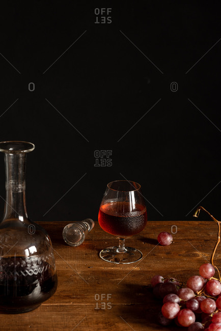 Still life composition with glass and decanter with cognac placed near bunch of red grapes on wooden table against black background