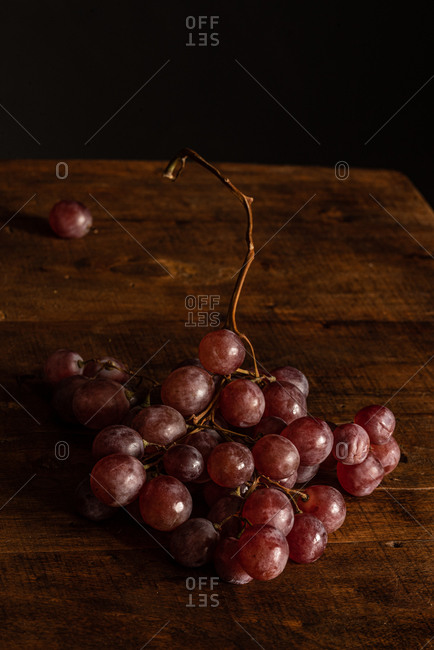 High angle of bunch of fresh ripe juicy red grapes placed on rustic wooden table in dark studio