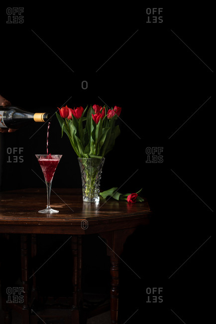 Unrecognizable person with bottle poring sparkling wine in glass placed on table with bouquet of red tulips on black background