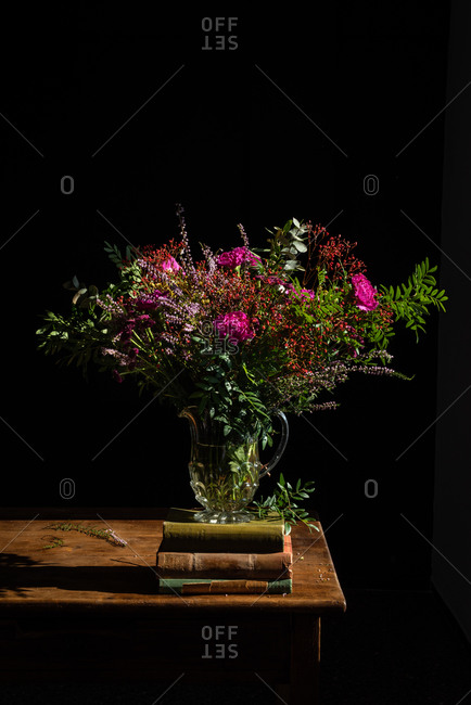 Bunch of assorted aromatic wildflowers placed in glass vase on rustic wooden table with pile of old books on black background in studio