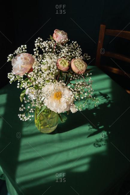 High angle of elegant bouquet of white gypsophila and pink peony flowers in glass vase placed on rustic table