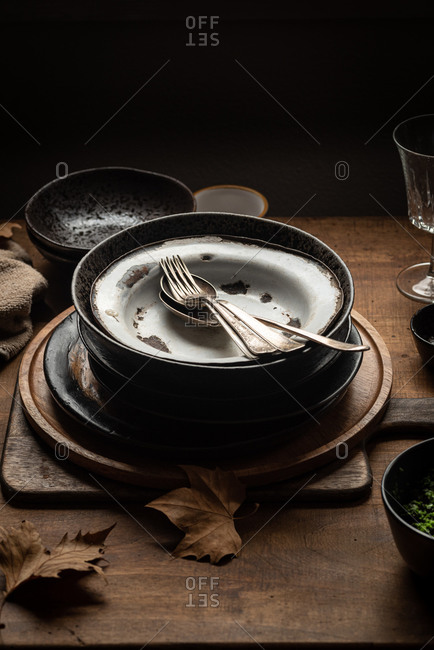 High angle of stack of old fashioned metal plates placed on wooden table with various utensils in dark country house