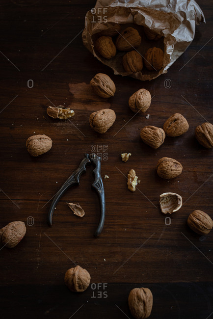 From above of pile of whole and cracked walnuts with kernels placed with nutcracker on dark wooden surface