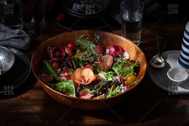 Healthy appetizing colorful salad with various fresh vegetables and herbs garnished with edible flowers served in wooden bowl on table setting for dinner