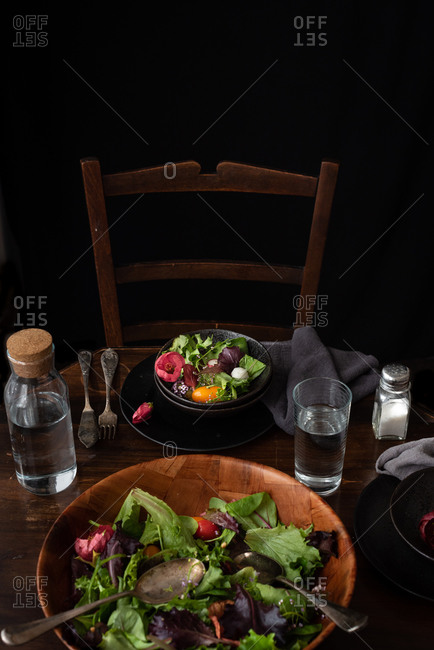 High angle of appetizing salad with fresh vegetables and green lettuce leaves served with glass of water on wooden table during dinner