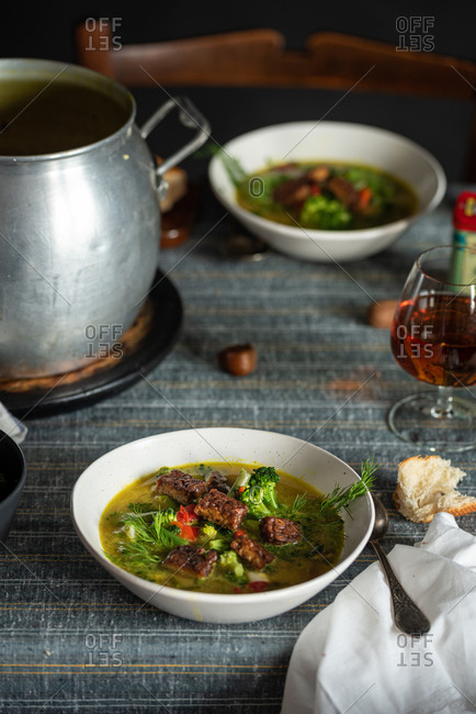 High angle of palatable hot soup with green herbs and meat served with glass of cognac on rustic table