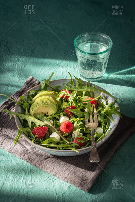 Delicious healthy salad with arugula and avocado garnished with cheese and fresh raspberries on green table