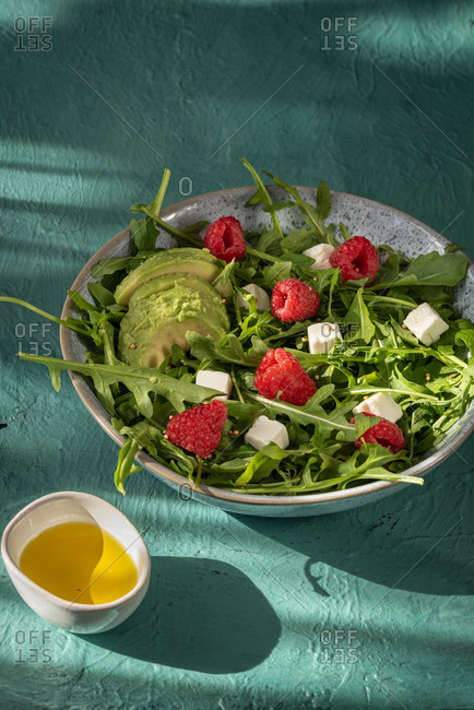 Delicious healthy salad with arugula and avocado garnished with cheese and fresh raspberries served with olive oil on green table