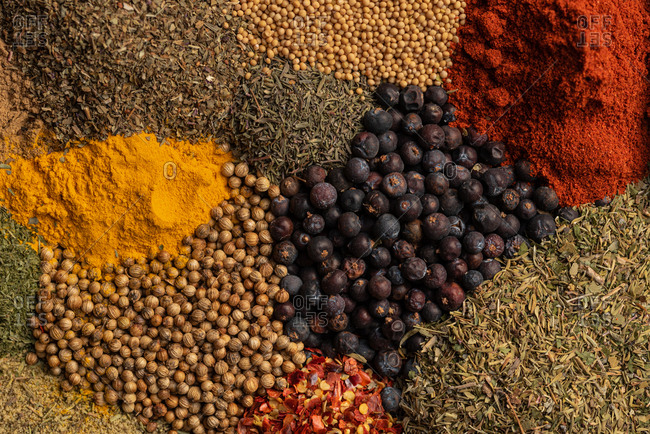 Top view closeup of pile of assorted aromatic dried spices including various types of pepper and herbs with paprika and turmeric powder scattered together
