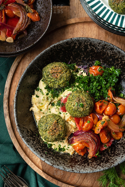 Top view of traditional Middle Eastern dish with vegetarian hummus and falafel served with vegetables and green herbs during dinner