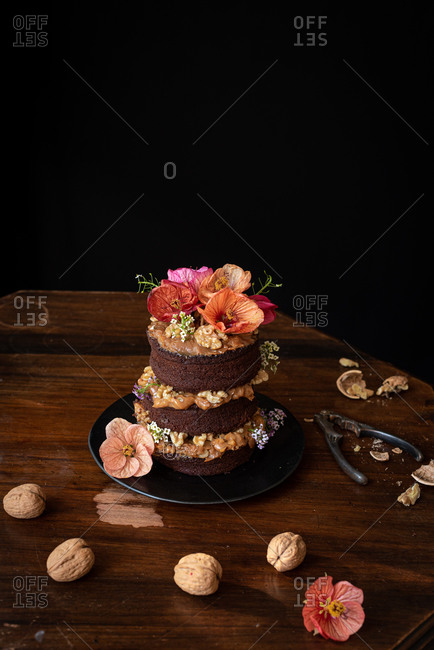 Delectable chocolate naked cake with cream and walnuts garnished with fresh flowers served on wooden table
